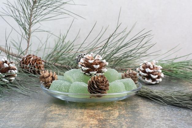 Eine glasplatte aus grüner marmelade und tannenzapfen. hochwertiges foto