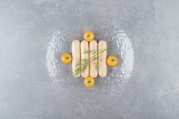 Eine glasplatte mit gekochten würstchen mit kirschgelben tomaten