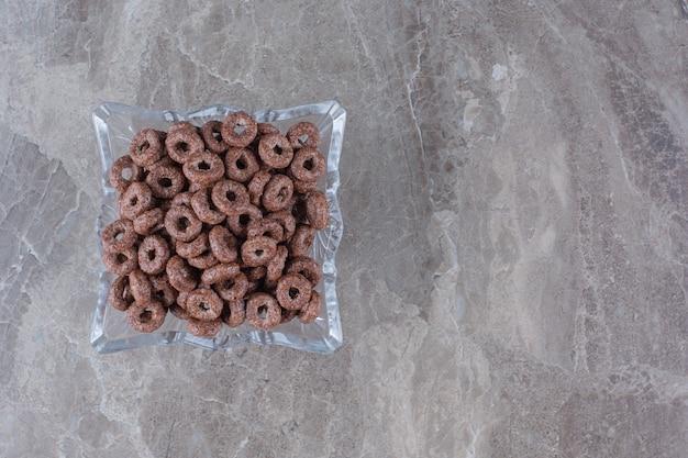 Eine glasplatte mit gesunden müsliringen aus schokolade zum frühstück.