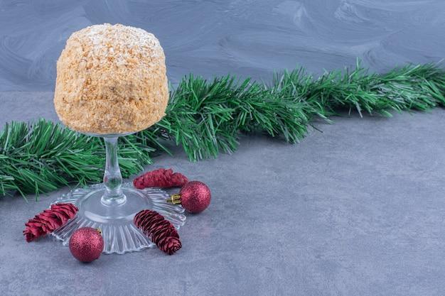 Eine glasplatte mit leckerem kuchen und weihnachtskugeln