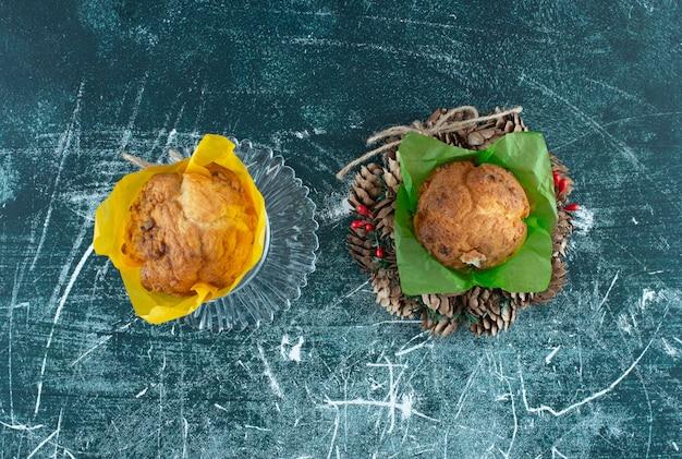 Eine glasplatte mit muffins und weihnachtskranz. foto in hoher qualität