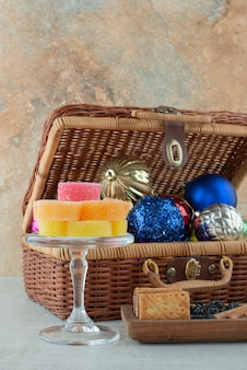 Eine glasplatte voll von zuckermarmelade und weihnachtsfestkugeln auf marmorhintergrund. hochwertiges foto