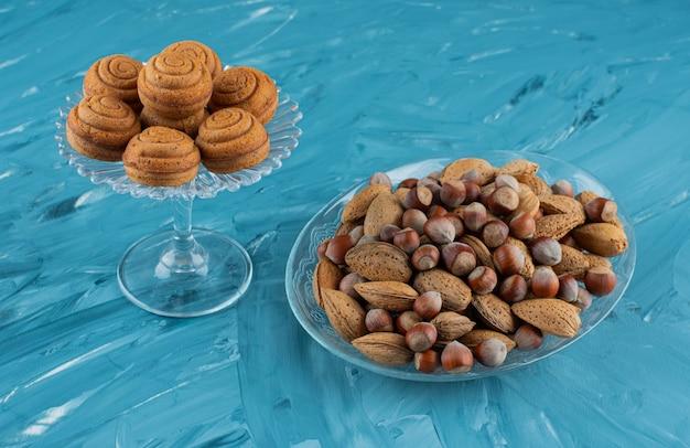 Eine glasplatte voller verschiedener arten von gesunden frischen nüssen auf einem blauen hintergrund.