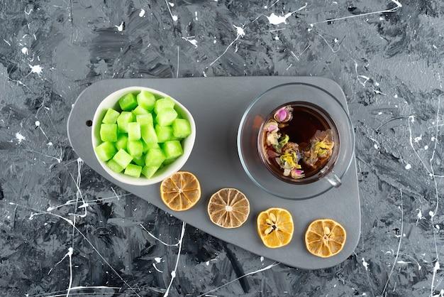 Eine glasschale heißen kräutertee mit zitronenscheiben und süßen köstlichkeiten