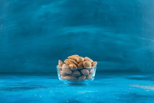 Eine glasschale mit geschälten mandeln auf der blauen oberfläche