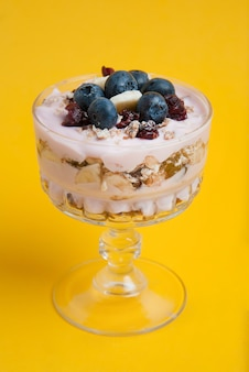 Eine glasschale mit haferflocken und früchten.