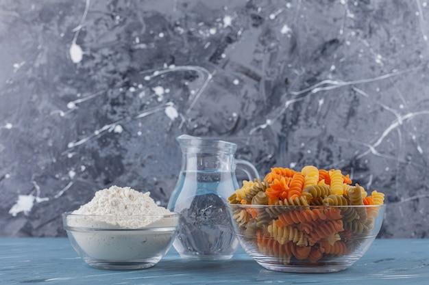 Eine glasschale mit mehrfarbigen rohen spiralnudeln mit einem krug und mehl.