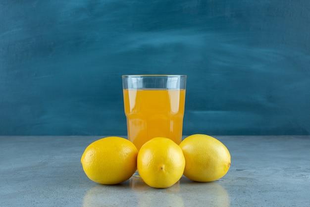 Eine glasschale orangensaft mit frischen zitronen.