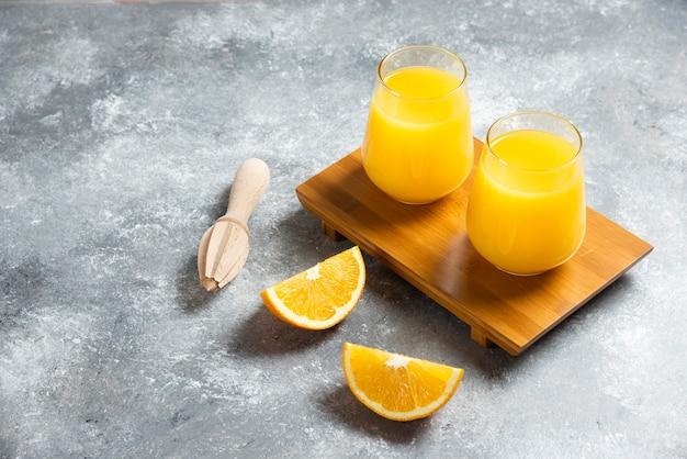 Eine glasschale orangensaft und eine holzreibahle.