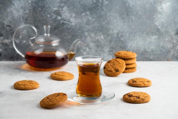 Eine glasschale tee mit leckeren keksen.