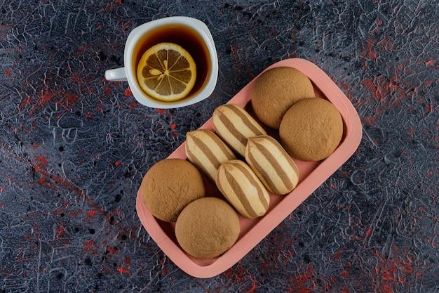 Eine glasschale tee mit süßen frischen keksen in einem brett auf einer dunkelheit