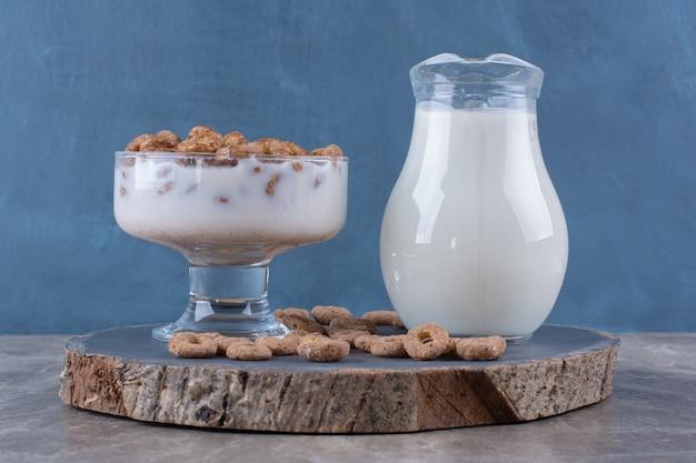 Eine glasschüssel mit gesundem joghurt mit knusprigen cerealien und einem glaskrug milch.