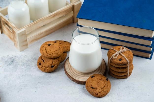 Eine glastasse milch mit schokoladenkeksen auf einem holzbrett.