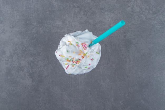 Eine glastasse süßer milchshake mit schlagsahne und streuseln. foto in hoher qualität