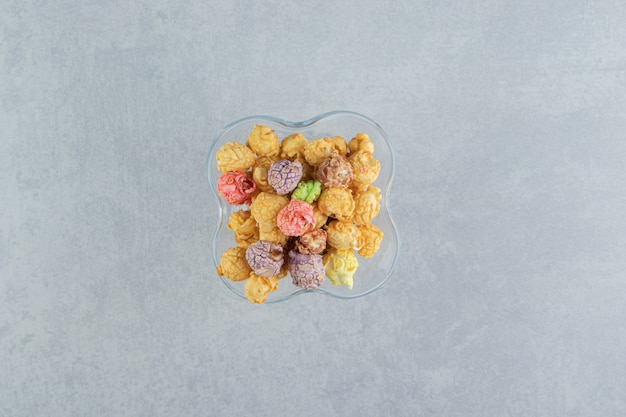 Eine glastasse süßes buntes popcorn.