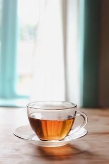 Eine glastasse tee auf einem holztisch
