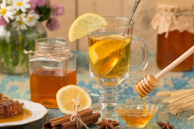 Eine glastasse tee mit zitrone und honig