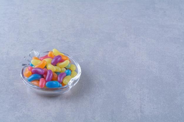 Eine glastasse voller bunter bohnenbonbons auf grauem hintergrund. hochwertiges foto