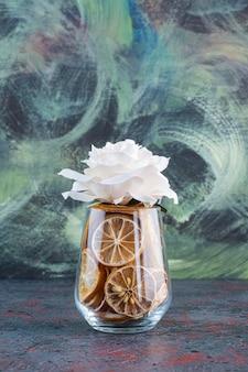 Eine glastasse voller getrockneter zitrone und rosa rose über dem kopf.