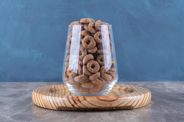 Eine glastasse voller schokoladenmüsliringe auf einem holzbrett.