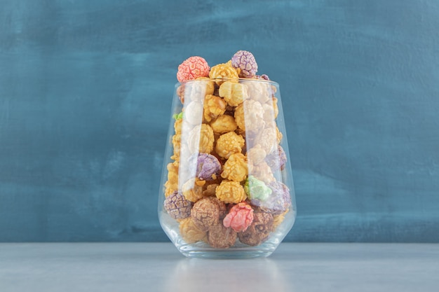 Eine glastasse voller süßem buntem popcorn.