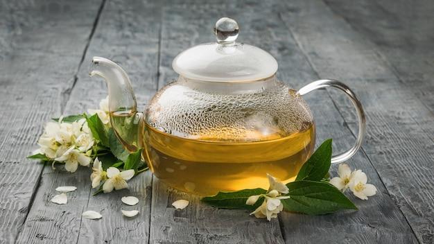 Eine glasteekanne gefüllt mit medizinischem tee mit jasminblüten. ein belebendes getränk, das ihrer gesundheit gut tut.