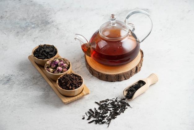 Eine glasteekanne mit holzschalen mit losen tees.