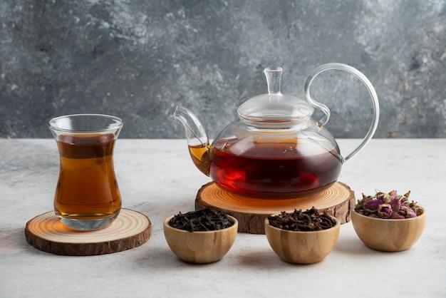 Eine glasteekanne mit tee auf holzbrett.