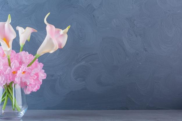 Eine glasvase mit einem strauß rosa schöner frischer blumen.