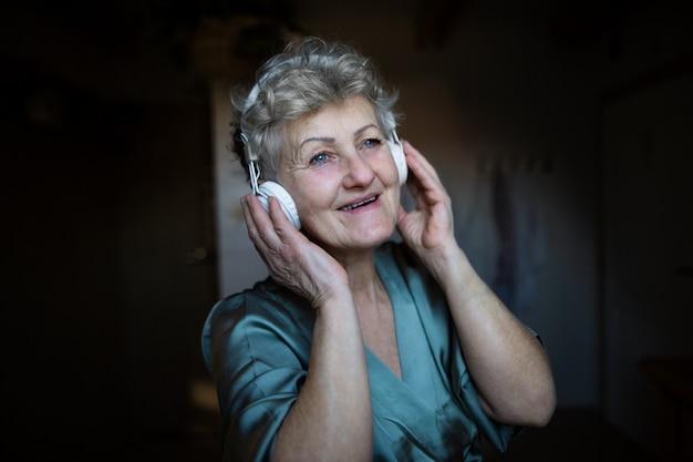 Eine glückliche ältere frau mit kopfhörern, die zu hause musik hören, sich entspannen und sich selbst pflegen.