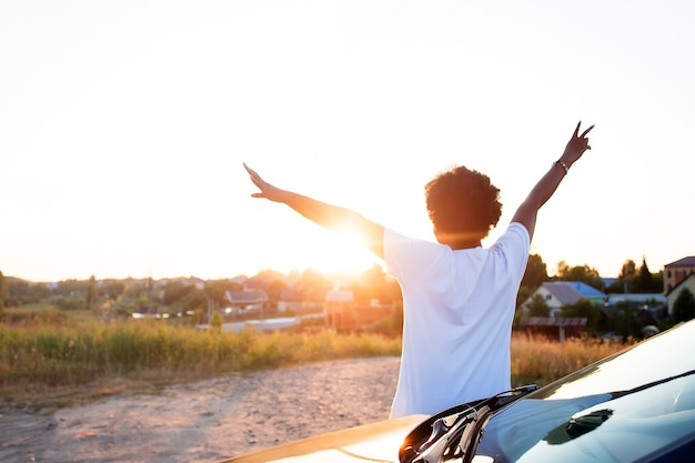 Eine glückliche afroamerikanische frau in der nähe des autos betrachtet den sonnenuntergang, lifestyle