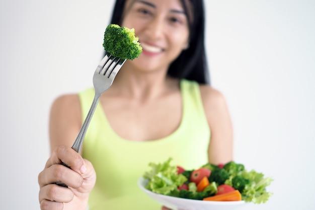 Eine glückliche asiatische frau mit einem gesunden salatteller, gabel mit einem großen brokkoli anhalten. essen für eine gute form