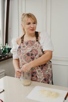 Eine glückliche blonde frau zerdrückt zitronensaft mit der hand in den mixbecher in der küche.
