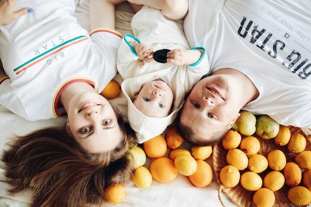 Eine glückliche dreierfamilie mag verschiedene früchte, liegt auf der couch und genießt das gemeinsame leben