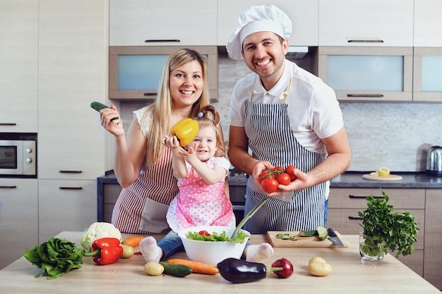 Eine glückliche familie bereitet essen in der küche zu