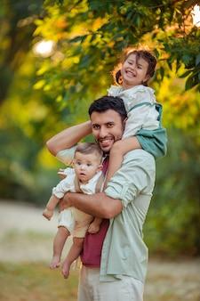 Eine glückliche familie. der lächelnde vater hält seine kleinen kinder, sohn und tochter, an händen und schultern fest, um im park spazieren zu gehen.