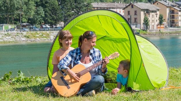 Eine glückliche familie, die am fluss zeltet, gitarre spielt und gemeinsam im zelt ein lied singt.