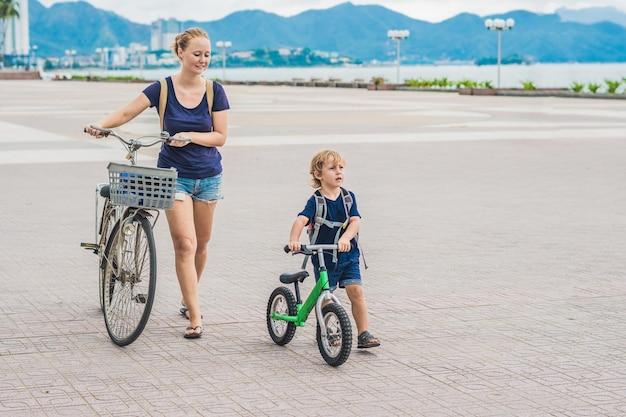 Eine glückliche familie fährt draußen fahrrad und lächelt. mutter auf einem fahrrad und sohn auf einem balancebike.