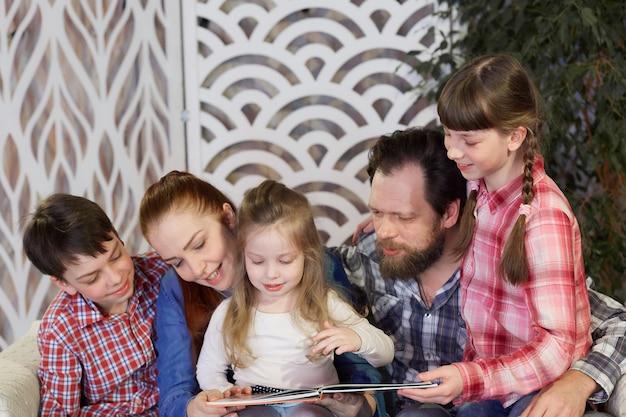Eine glückliche familie liest bücher zu hause. freizeit mit der familie