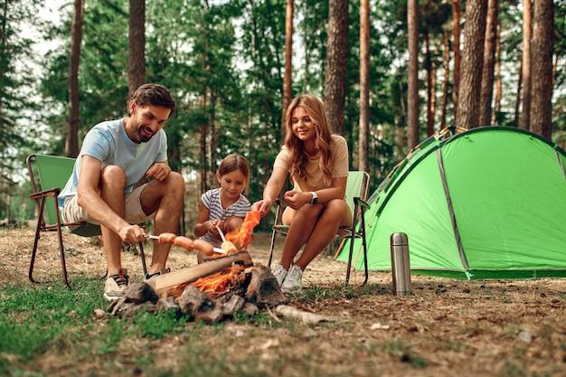 Eine glückliche familie mit einem kind auf einem picknick sitzt am feuer in der nähe des zeltes und grillt einen grill in einem kiefernwald. camping, erholung, wandern.