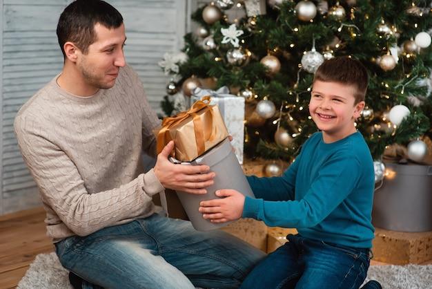 Eine glückliche familie mit einem kind feiert ein neues jahr oder weihnachten. vater und sohn sitzen zu hause auf dem boden neben dem weihnachtsbaum und tauschen geschenke aus