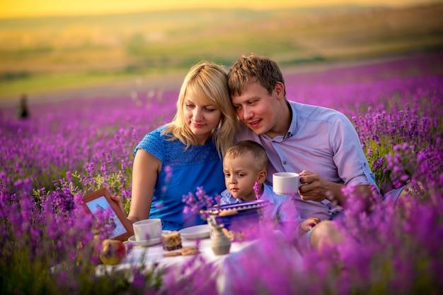 Eine glückliche familie mit einem kleinen jungen geht und spielt auf einem schönen lavendelfeld. familienurlaub