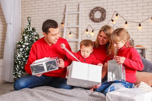 Eine glückliche familie mit geschenken an weihnachten