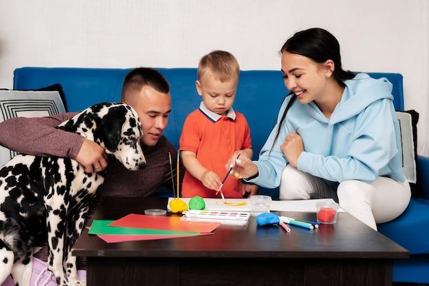 Eine glückliche familie mit ihrem sohn und hund dalmatiner sitzt zu hause am tisch und malt und modelliert mit plastilin