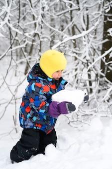 Eine glückliche familie mit kindern hat spaß daran, die winterferien im verschneiten winterwald zu verbringen. kleines kind junge fröhlich spielt
