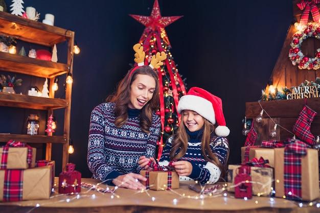 Eine glückliche familie mutter und kind packen weihnachtsgeschenke