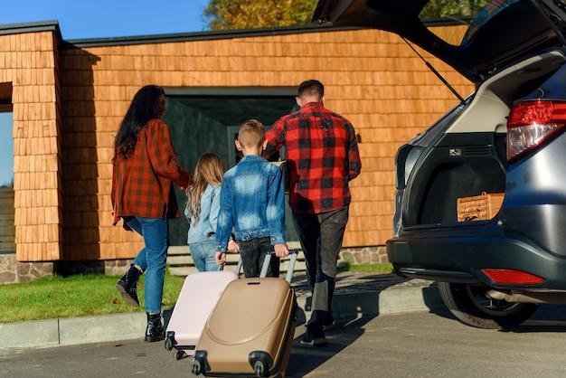 Eine glückliche familie packt ihr gepäck aus dem kofferraum eines autos aus, nachdem sie in ein neues zuhause gezogen ist.