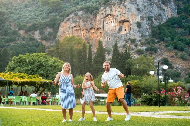 Eine glückliche familie steht auf dem hintergrund eines berges in der stadt dalyan.people in der nähe von lykischen gräbern in der türkei.