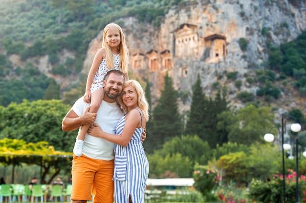 Eine glückliche familie steht auf dem hintergrund eines berges in der stadt dalyan.