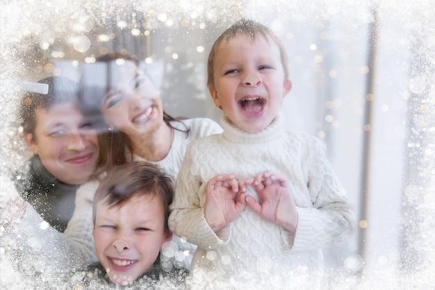 Eine glückliche familie steht hinter einem schneebedeckten fenster, lacht, kinder verziehen das gesicht, zeigen ihre zungen.